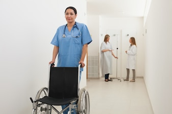 Nurse pushing empty wheelchair