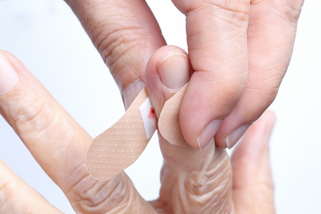 Nurse putting adhesive bandage on elderly woman hand