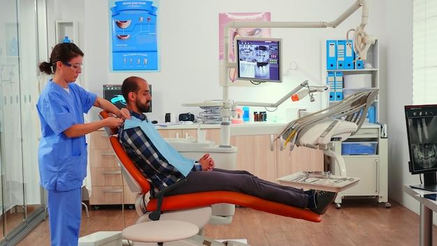 歯科医が患者の歯の手術の準備をするのを待っている、口腔病学的検査の前に男性に歯科用よだれかけを置く看護師。現代の歯科矯正クリニックで働く看護師。