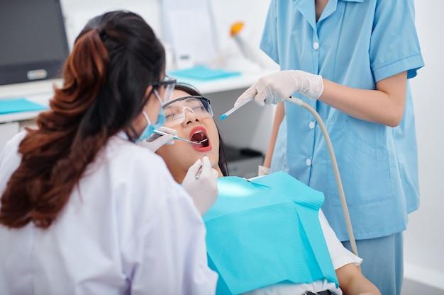 치과 의사가 거울과 핀셋으로 치아를 검사할 때 여성 환자의 입에 타액 배출기를 넣는 간호사