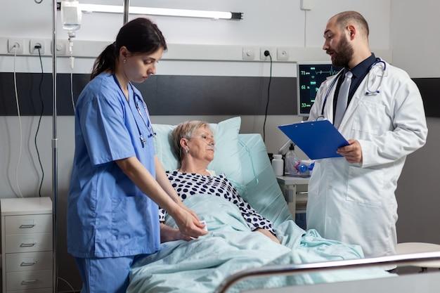 酸素濃度計から血中酸素飽和度を読み取る看護師