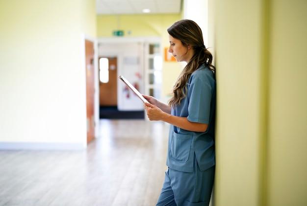 복도에서 의료 기록을 읽는 간호사