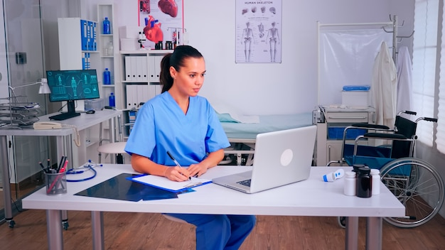 Nurse receving health results of patients, taking notes on clipboard, reading on laptop in hospital. medical physician in medicine uniform writing list of consulted, diagnosed patients, making researc
