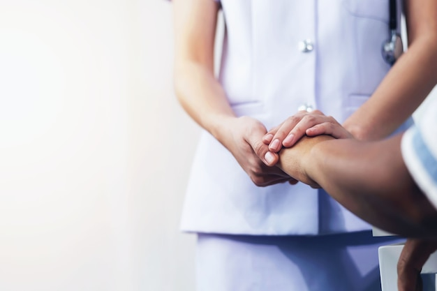 A nurse shaking hands to encourage the patient