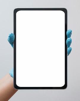 空白のタブレットのクローズアップを示す看護師