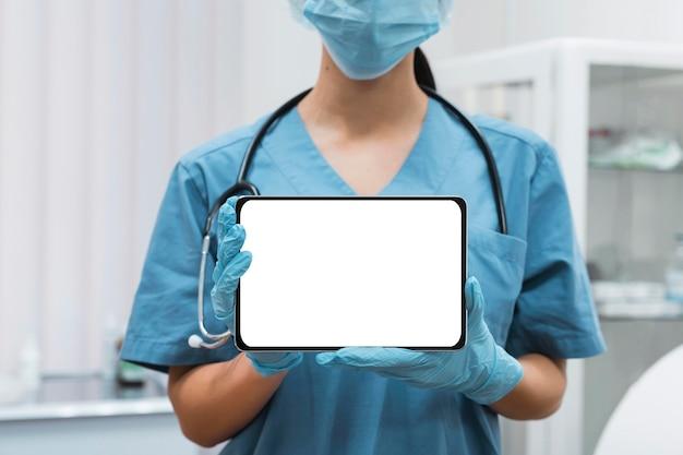 空白のタブレットを見せている看護師
