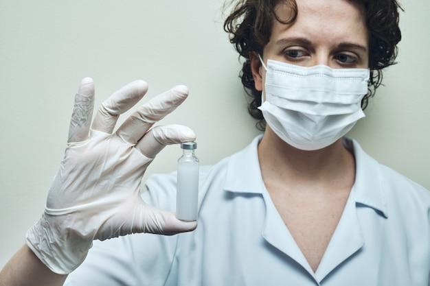간호사 장갑과 마스크와 백신 앰플을 보여주는.