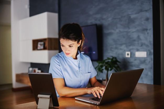 간호사는 집에 앉아서 온라인 조언을 제공합니다. 테이블에는 태블릿과 노트북이 있습니다.