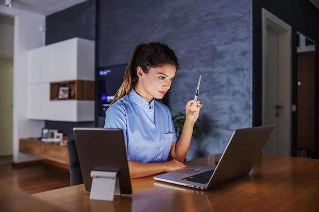 自宅に座って、治療法の注射器を持って、インターネットを介してアドバイスを与える看護師。