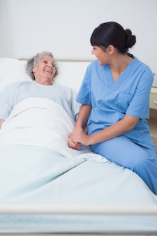 Nurse sitting on the medical bed next to a patient