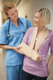 간호사 팔 슬링에 환자와 함께 웃 고