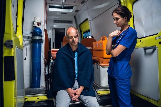 救急車の端に座っている患者の横に立っている看護師。