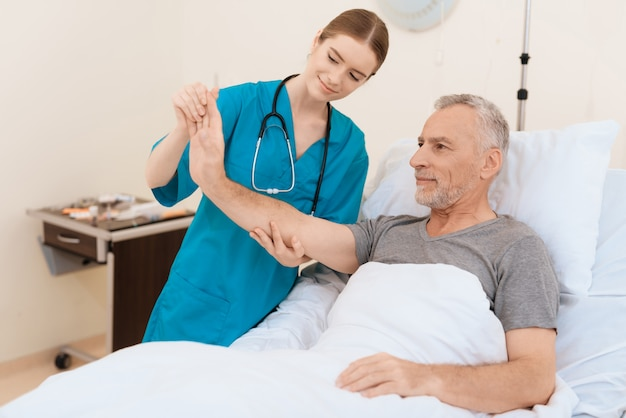 The nurse stands next to the old man and examines his hand.