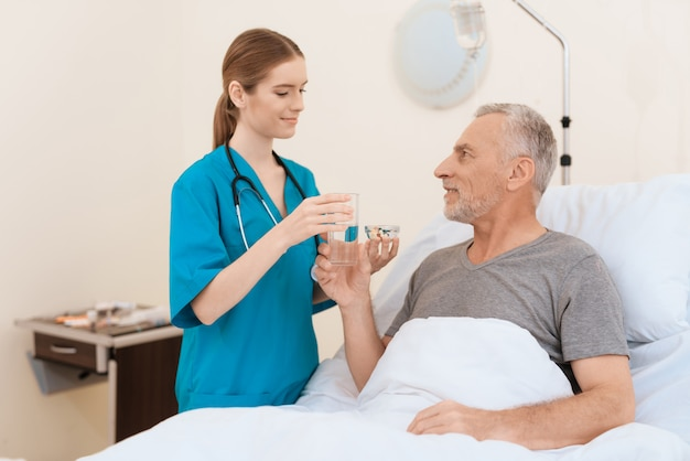 Nurse stands next to the old man and gives him water and pills