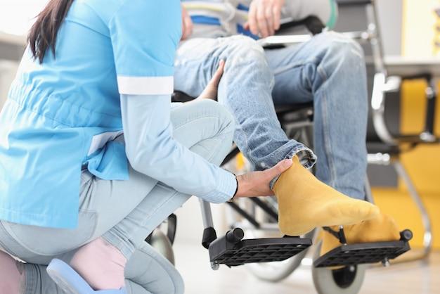 간호사는 휠체어에 장애인 다리를 지원합니다