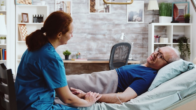 Медсестра сидит рядом с больным стариком, который лежит на больничной койке в доме престарелых