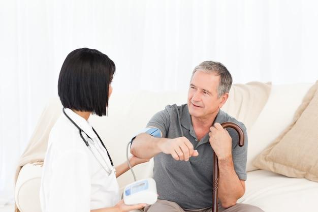 Nurse taking blood pressure of her patient
