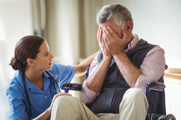 Nurse taking care of sad senior man