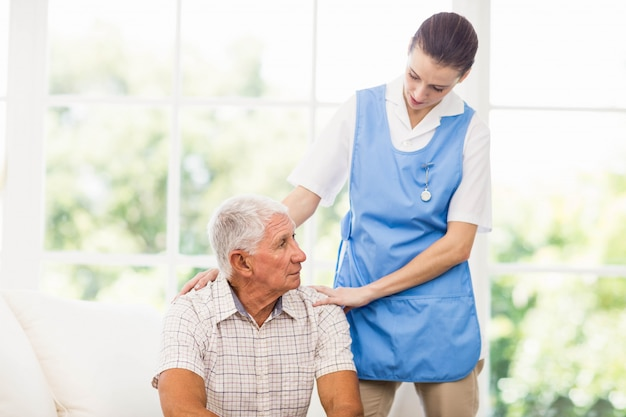 Nurse taking care of sick elderly patient at home