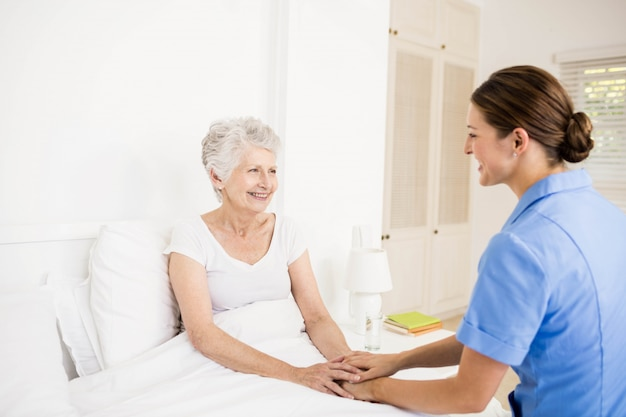 Nurse taking care of suffering senior patient at home