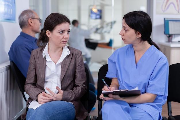 Медсестра делает заметки в буфере обмена о стоматологических проблемах пациента, ожидая ортодонта, сидящего на ...