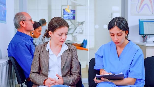 간호사는 치과 진료소 대기실의 의자에 앉아 치과 교정 의사를 기다리는 환자의 치과 문제에 대해 클립보드에 메모합니다. 여성에게 의료 절차를 설명하는 조수.