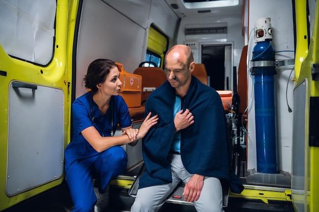 Nurse talking friendly to an injured man in a blanket in an ambulance car.