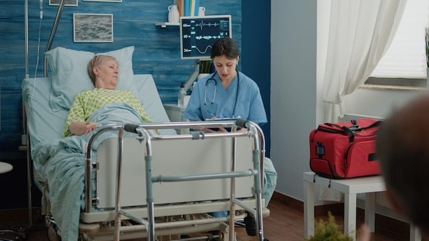 Nurse talking to retired patient with sickness in nursing home