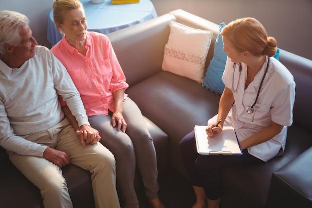 Nurse talking to senior couple