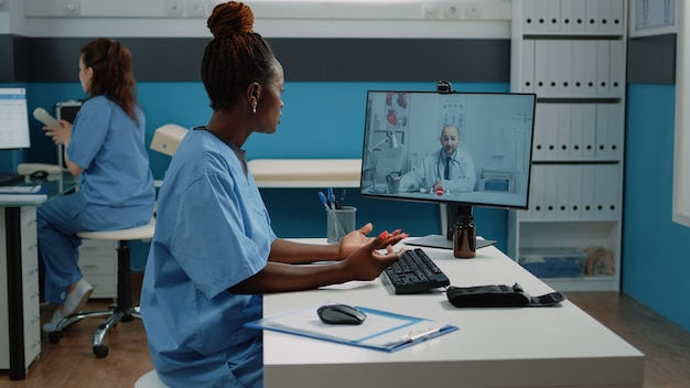 Медсестра разговаривает с врачом по видеозвонку в кабинете
