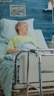요양원에서 병이 있는 은퇴한 환자와 이야기하는 간호사