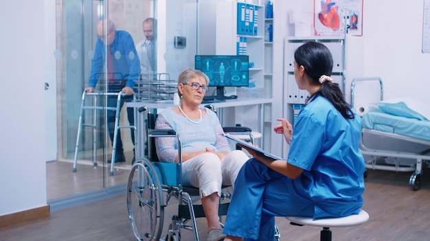 Nurse talking with senior woman with walking disabilities sitting in a wheelchair, into a private modern recovery clinic or hospital. handicapped old retired patient medical consultation and advice