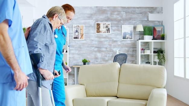 老婆がナーシングホームの部屋を歩くのを手伝う看護師チーム。介護者とソーシャルワーカー