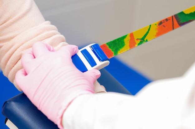 Медсестра затягивает ремни безопасности на руке, чтобы взять кровь из вены на анализ.