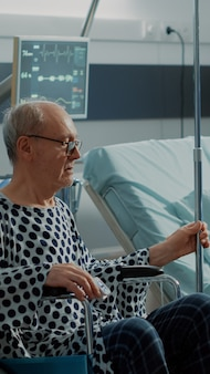 車椅子の老人患者を手術室に運ぶ看護師