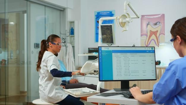 歯科医が診察前に口腔病学の椅子で患者と話している間、看護師がコンピューターで入力し、予約を取ります。現代の口腔病学クリニックで一緒に働く歯科医と看護師