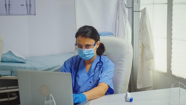 코로나바이러스 동안 의료용 장갑을 끼고 노트북에 타이핑하는 간호사. 병원 캐비닛에서 의료 서비스 상담 치료 검사를 제공하는 의학 전문 의사