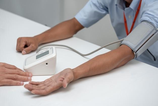 The nurse uses a patient's arm pressure gauge.