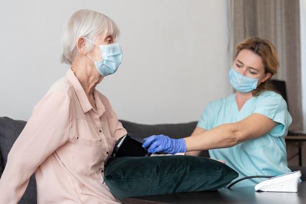 노인 여성의 혈압 모니터를 사용하는 간호사