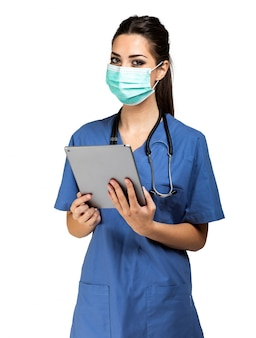 Nurse using a digital tablet and wearing a mask isolated on white