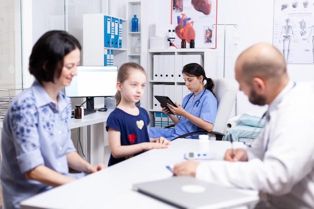 의사가 병원 사무실에서 아픈 아이를 상담하는 동안 간호사는 태블릿 pc를 사용합니다.
