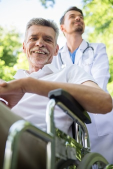 Nurse walking with senior patient in wheelchair in garden.