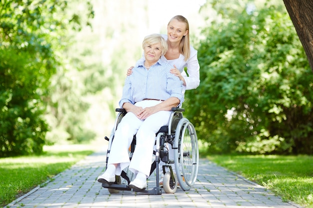 Nurse walking with senior patient in wheelchair