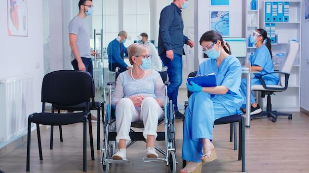 Медсестра в маске против коронавируса делает заметки в буфере обмена во время разговора с пожилой женщиной-инвалидом в инвалидной коляске в зоне ожидания больницы. пациенты на приеме.