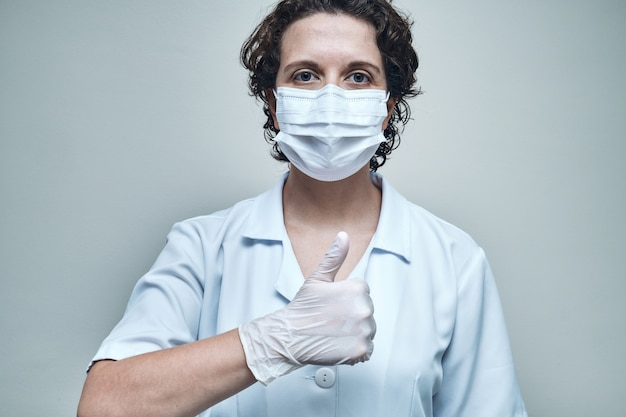 Медсестра в маске и перчатках показывает палец вверх.