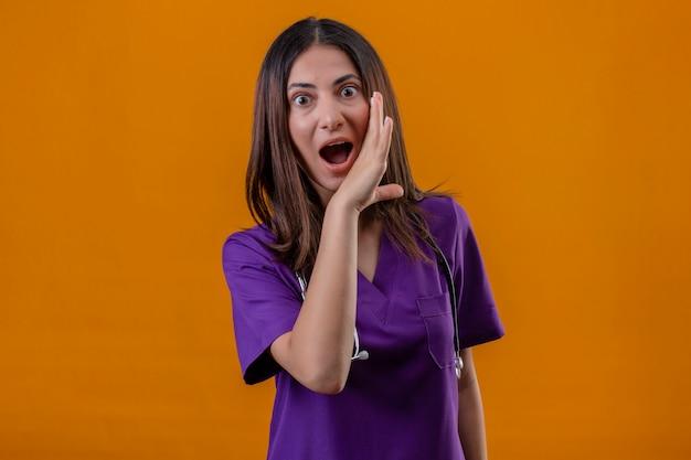 Infermiera che indossa l'uniforme medica e lo stetoscopio con una mano vicino alla bocca che racconta un segreto guardando sorpreso in piedi su un arancio isolato