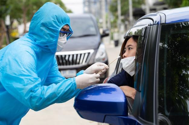 전체 보호 장구에 ppe 슈트 또는 의료진을 착용 한 간호사는 차 안에서 여성 운전자로부터 샘플을 채취합니다. 코로나 바이러스 covid-19에 대한 드라이브 스루 테스트