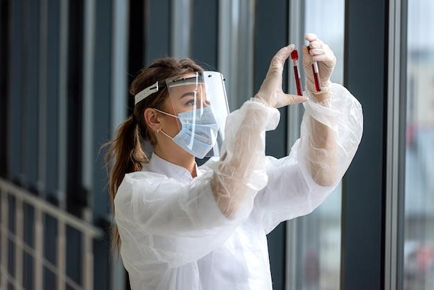 Медсестра в скрабах держит и смотрит на пробирку с кровью в лаборатории