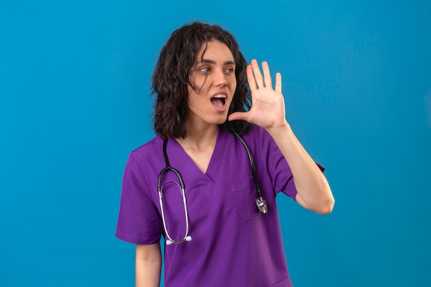 Infermiera che indossa l'uniforme e lo stetoscopio che grida chiamando qualcuno con la mano vicino alla bocca sul blu isolato