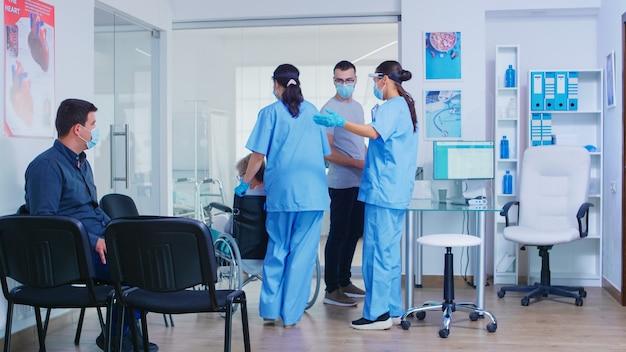 병원 대기실에서 코비드-19에 대비한 바이저를 착용한 간호사가 환자와 이야기하고 있습니다. 보조자는 얼굴 마스크와 멸균 장갑을 끼고 휠체어를 탄 장애인 노인 여성을 밀고 있습니다.